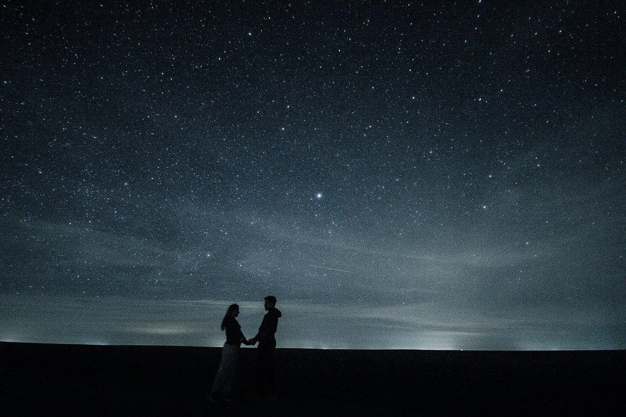 Couple homme-femme face à un immense ciel étoilé